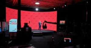 Encore's presentation stage with a presenter presenting while being filmed by large moving camera