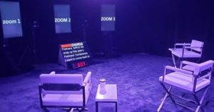 This image is a stage with surrounding chairs facing a tv screen with words for presenters to talk through
