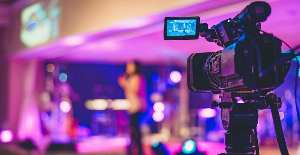 Camera focused on presenter on broadcast stage