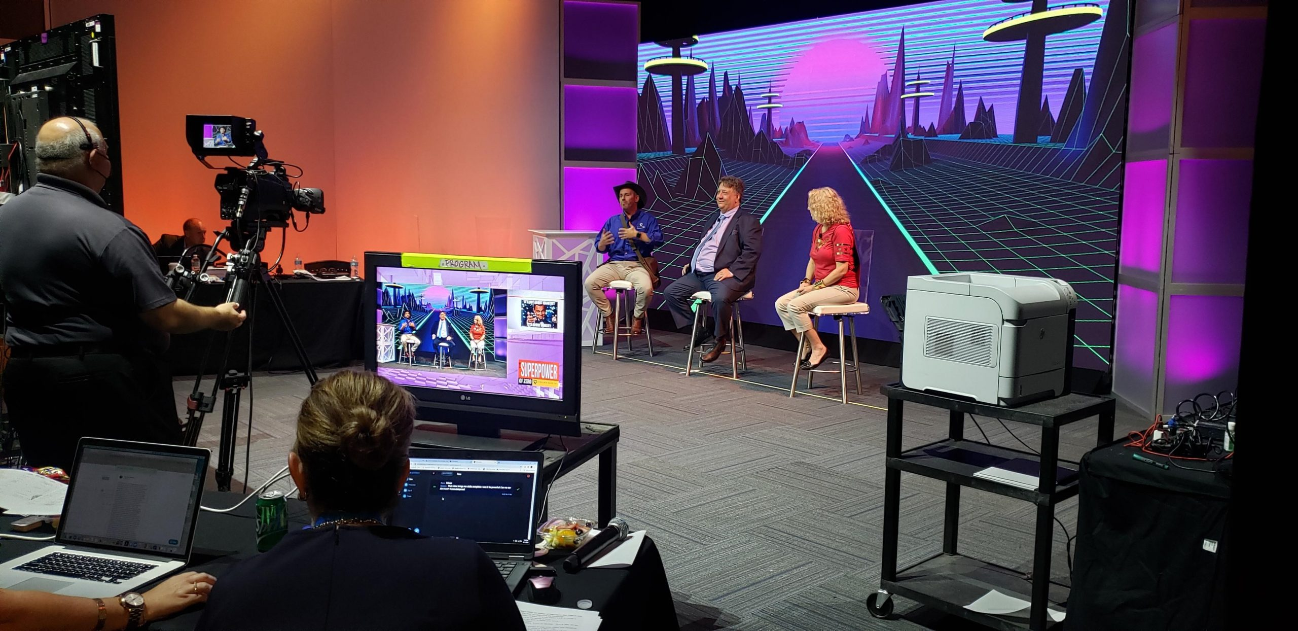 Panelists are filmed in front of a branded stage, while technical team are vision mixing the content into the virtual event